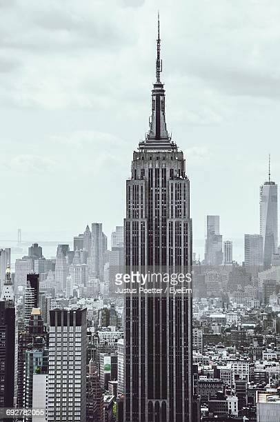empire state building in city against sky - empire state building stock pictures, royalty-free photos & images