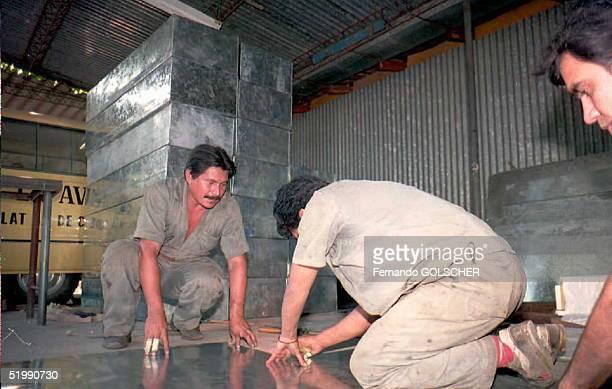 Empleados de una funeraria trabajan 11 AGOSTO en la construcion de ataudes para la repatriacion a sus paises de origen de los cadaveres de pasajeros...