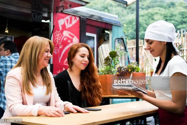 de tewerkgestelde vrouw van de voedsel vrachtwagen neemt de orde van belangrijke en mooie klanten - food truck stockfoto's en -beelden