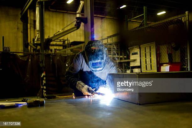 Employee Alex Hannan welds a metal cabinet at the Giese Manufacturing Co in Dubuque Iowa US on Thursday Feb 14 2013 The US Federal Reserve is...