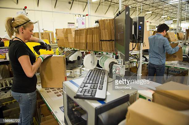 Employee Alexis Debroeck left scans a box before shipment at the Amazoncom Inc distribution center in Phoenix Arizona US on Monday Nov 26 2012 US...