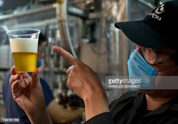 Employee Angel rodriguez checks the beer during the bottling process in the Calavera craft brewery on July 20 in Tlanepantla Mexico State Producers...