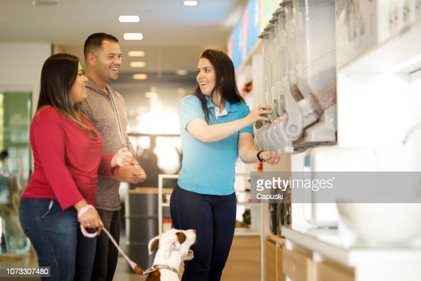 employee assisting customers at pet salon - food distribution stock pictures, royalty-free photos & images