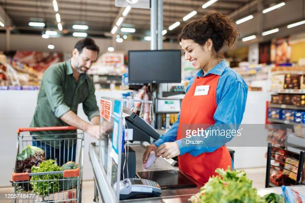 employee at cash register in supermarket, serving the customer - cashier stock pictures, royalty-free photos & images