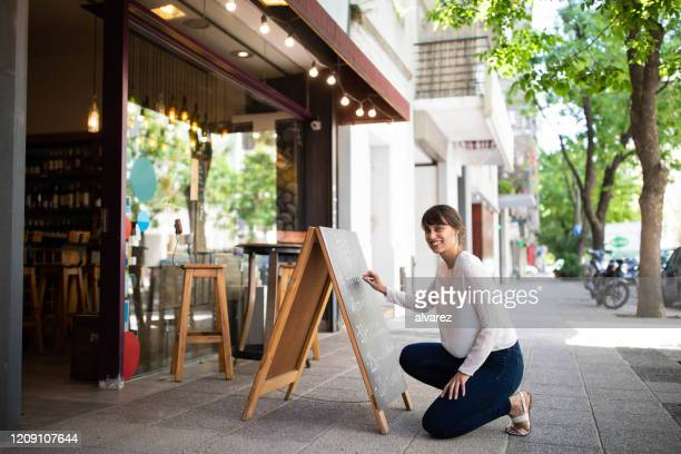 employee at chalkboard outside wine shop - small business stock pictures, royalty-free photos & images
