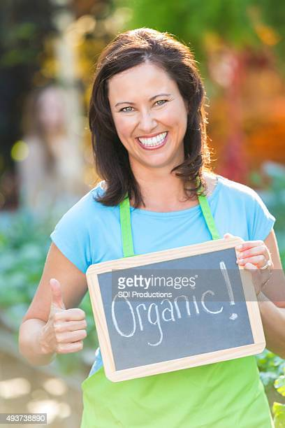 Employee at local market holding ORGANIC sign