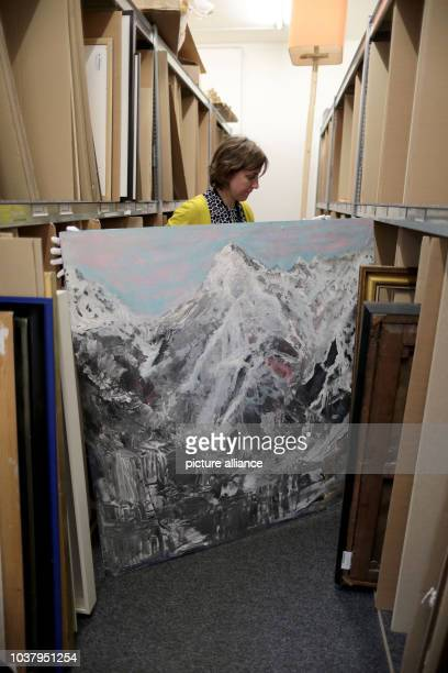 Employee at the Van Ham art auction house Annika Norpoth pulls the acrylic painting 'Spirit of Freedom Nr 10'by Helge Achenbach from a shelf in...