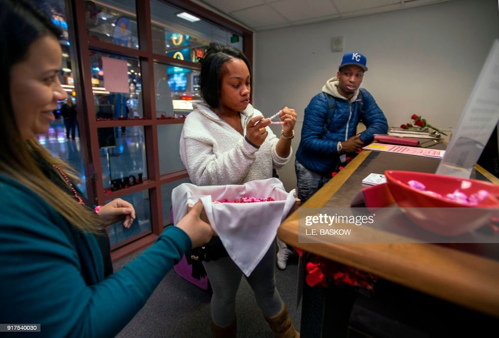 Employee Bianca Dozal offers a bracelet gift to Teaira Thompson and James Anderson of Burlington, Iowa, who completed their paperwork as the Clark County Clerk's Office operates a temporary pop-up marriage license office at McCarran International Airport in Las Vegas on February 12, 2018. The Las Vegas airport has given new meaning to rushing to make a connection, offering quickie wedding licenses for lovebirds desperate to get hitched on Valentine's Day. Clark County, the authority that administers Sin City's weddings, has opened a pop-up marriage license bureau by a baggage carousel at McCarran International Airport. E. Baskow / TO GO WITH AFP STORY, 'Valentines get quickie marriage licenses at Las Vegas airport'