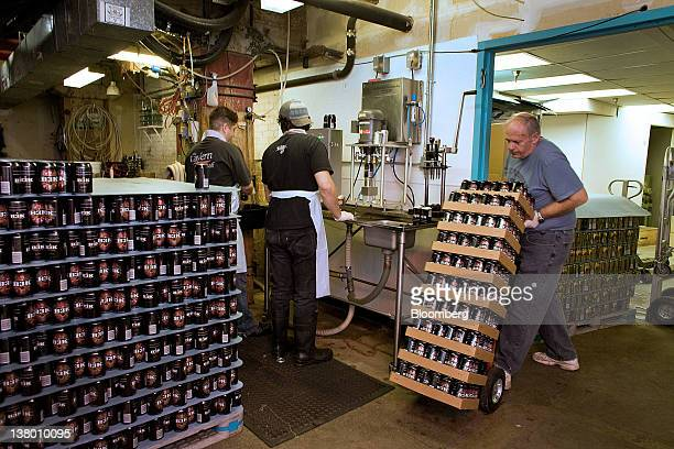Employee Bill Dodge right moves a dolly full of recently canned beer while Eric Erman center and Michael Knez continue canning Wynkoop Brewing Co's...