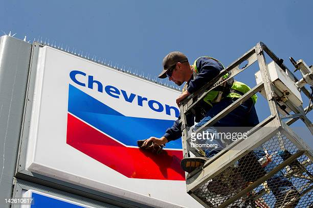Employee Brandon Scully works on a Chevron Corp sign at a gasoline station in San Francisco California US on Friday April 6 2012 Gasoline slid to a...