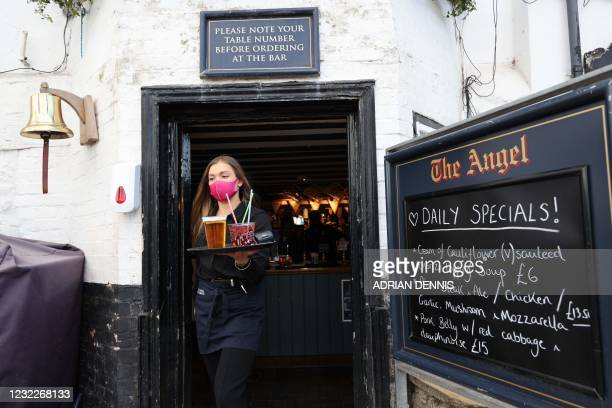 Employee Charlotte Fisher serves drinks to customers at The Angel on the Bridge pub in Henley on Thames, west of London, on April 12, 2021 as...