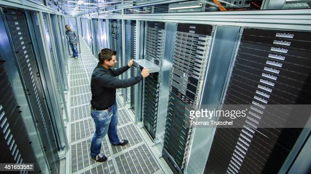 Employee checking a server rack at the new data center of TSystems a subsidiary of Deutsche Telekom AG on July 01 in Biere Germany TSystems is the...
