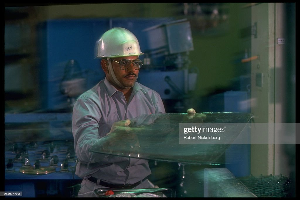Employee checking safety glass for flaws : News Photo