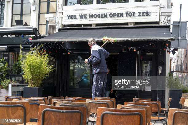 Employee cleans a terrace on the Amstel in Amsterdam on April 24 after the Dutch cabinet decided that the terraces for outdoor services can reopened...