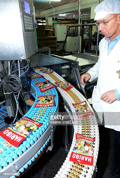 A employee controls the production process of 'Goldbaeren' fruit gums at the HARIBO candy factory on January 24 2013 in Bonn western Germany AFP...