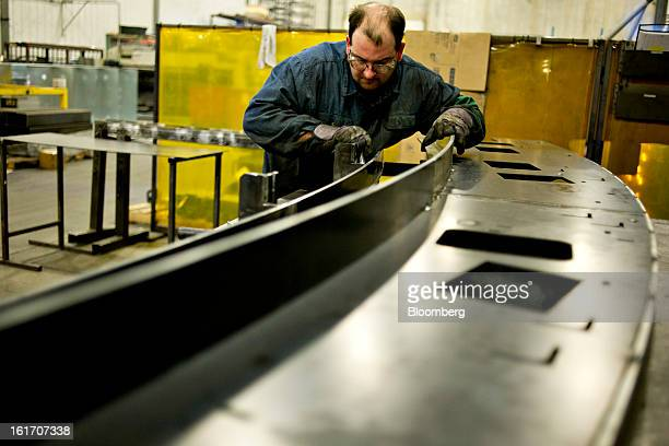 Employee Corey DeMoss assembles a railing assembly for an escalator at the Giese Manufacturing Co in Dubuque Iowa US on Thursday Feb 14 2013 The US...