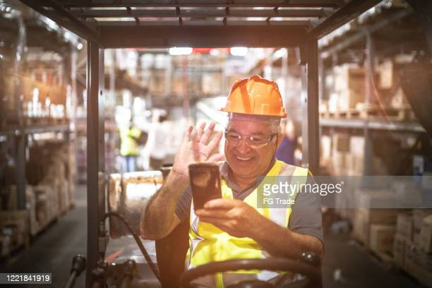 employee doing a video call on mobile phone at warehouse / industry - video still stock pictures, royalty-free photos & images