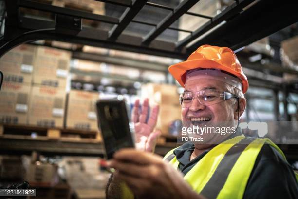 employee doing a video call on mobile phone at warehouse / industry - candid forum stock pictures, royalty-free photos & images