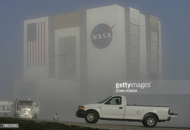 A NASA employee drives a truck past the fog enshrouded Vehicle Assembly Building early morning on February 5 2008 at the Kennedy Space Center in Cape...