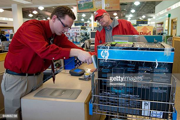 Employee Dustin Coffman left scans a Hewlett Packard computer being purchased by John Hancock right inside a Micro Center store Columbus Ohio US on...