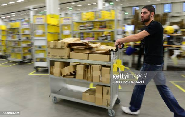 A employee employee ferries packed goods for shipment at US online retail giant Amazon's Brieselang logistics center west of Berlin on November 11...
