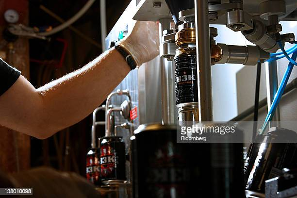 Employee Eric Erman uses a can seamer to seal the lid on a can of Wynkoop Brewing Co's B3K Black Lager at the company's facility in Denver Colorado...