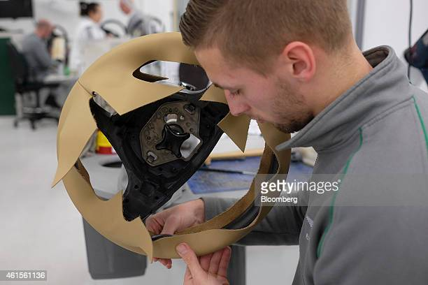 A employee fits leather to a steering wheel as he works in the upholstery department at the Bentley Motors Ltd workshop in Crewe UK on Wednesday Jan...