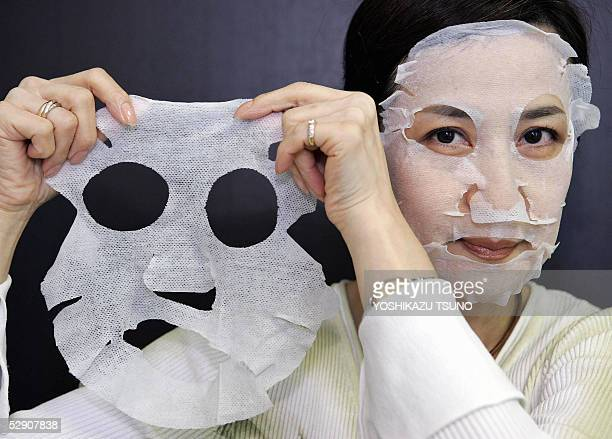 Employee for Japanese cosmetics giant Shiseido Shinobu Sugiyama displays an antiaging sheeted mask called the Elixir Lifting Net Mask which contains...