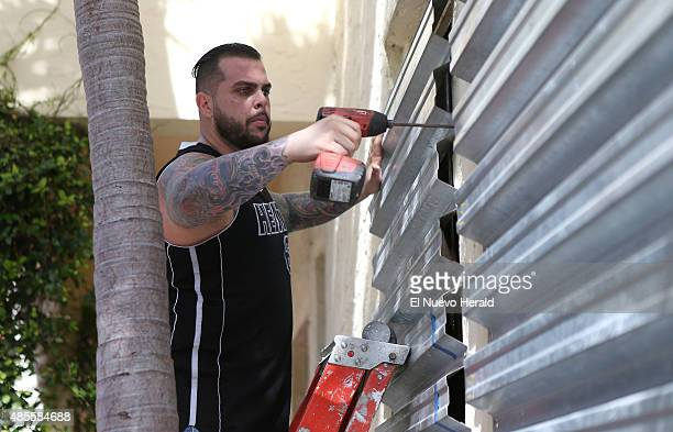 Employee from Joe's Stone Crab, Jordan Garcia, installing shuttles in preparation for Tropical Storm Erika on Friday, August 28 in Miami Beach.
