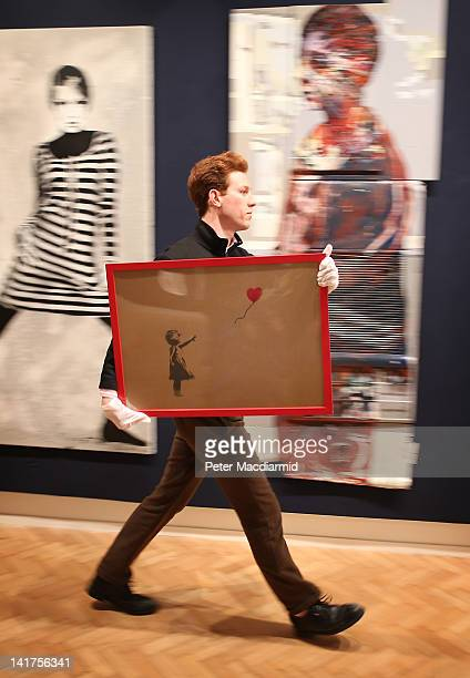 Employee George Foren holds Banksy's 'Girl and Balloon' which was painted on an Ikea frame at Bonhams auctioneers on March 23 2012 in London England...