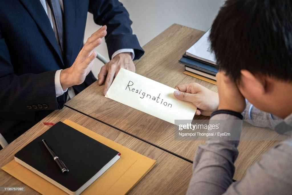 Employee Giving Resignation Letter To Manager At Office ...