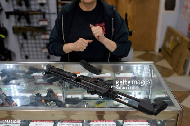 Employee Gorety Mejia takes down a HK MP5 for a customer at Full Armor Firearms store in Houston, Texas on June 17, 2021. - Governor Greg Abbott...