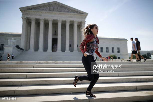 CNBC employee Grace Williams runs across the US Supreme Court plaza carrying an opinion to a news correspondent as the court handed down decisions...