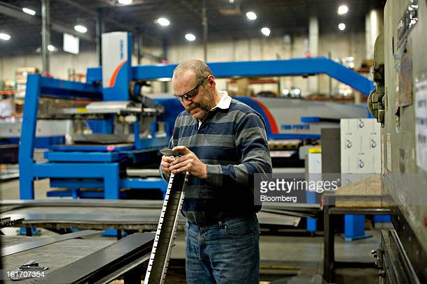 Employee Greg Shaffer uses a gauge to check the accuracy of a bend as he works at a press break at the Giese Manufacturing Co in Dubuque Iowa US on...