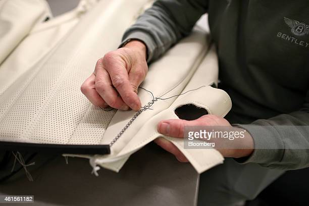 A employee handsews a customized stitch pattern into the back of a leather seat as he works in the upholstery department at the Bentley Motors Ltd...