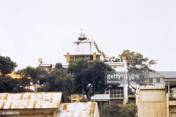 A CIA employee helps Vietnamese evacuees onto an Air America helicopter from the top of 22 Gia Long Street a half mile from the US Embassy