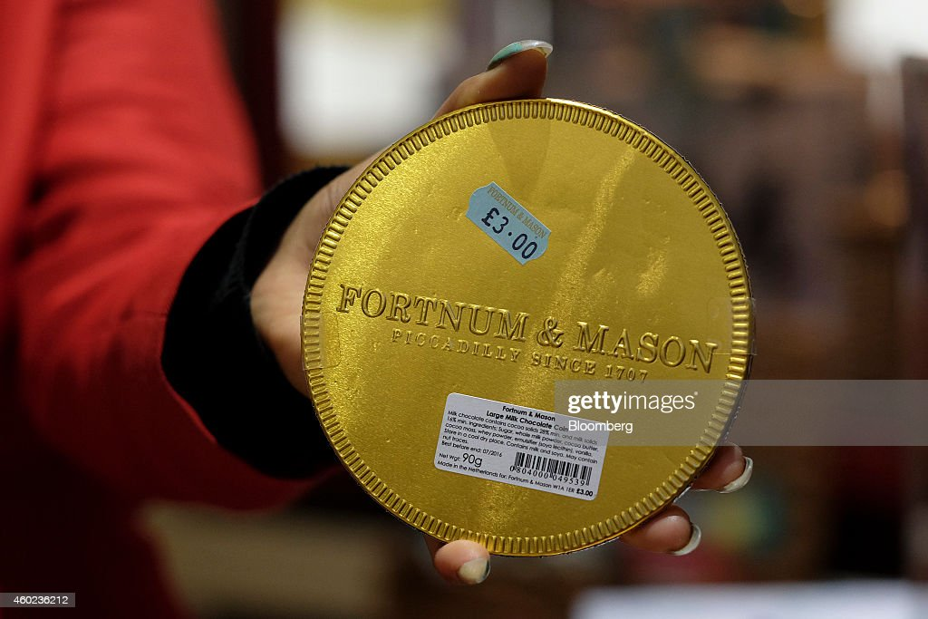 A employee holds a giant gold chocolate coin displayed for sale inside a pop-up store, operated by Fortnum & Mason Plc, during a seasonal Christmas event at Somerset House in London, U.K., on Tuesday, Dec. 9, 2014. The British will be the biggest spenders in Europe on Christmas gifts this year, according to a study commissioned by Dutch bank ING Groep NV. Photographer: Simon Dawson/Bloomberg via Getty Images