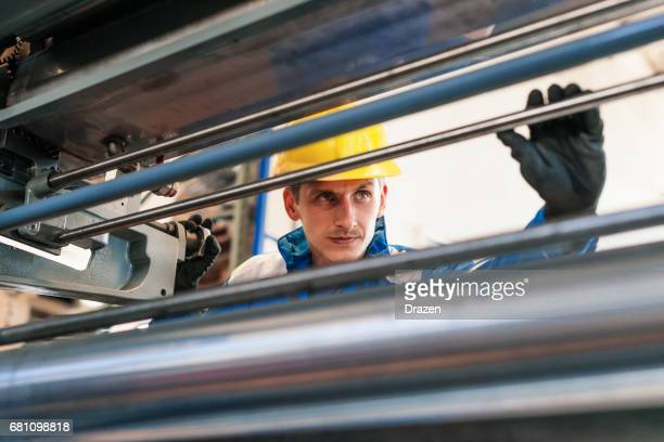 Employee in blue uniform working in factory - taking measures of roll bars