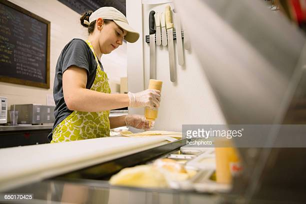 employee in general store preparing food in kitchen - heshphoto stock-fotos und bilder