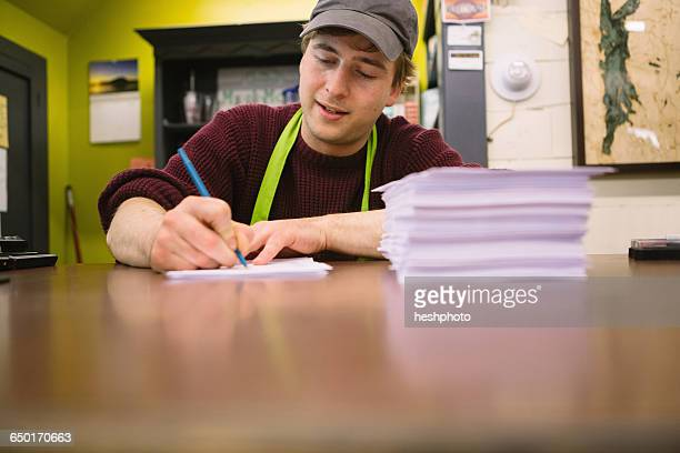 employee in general store writing notes in office - heshphoto photos et images de collection