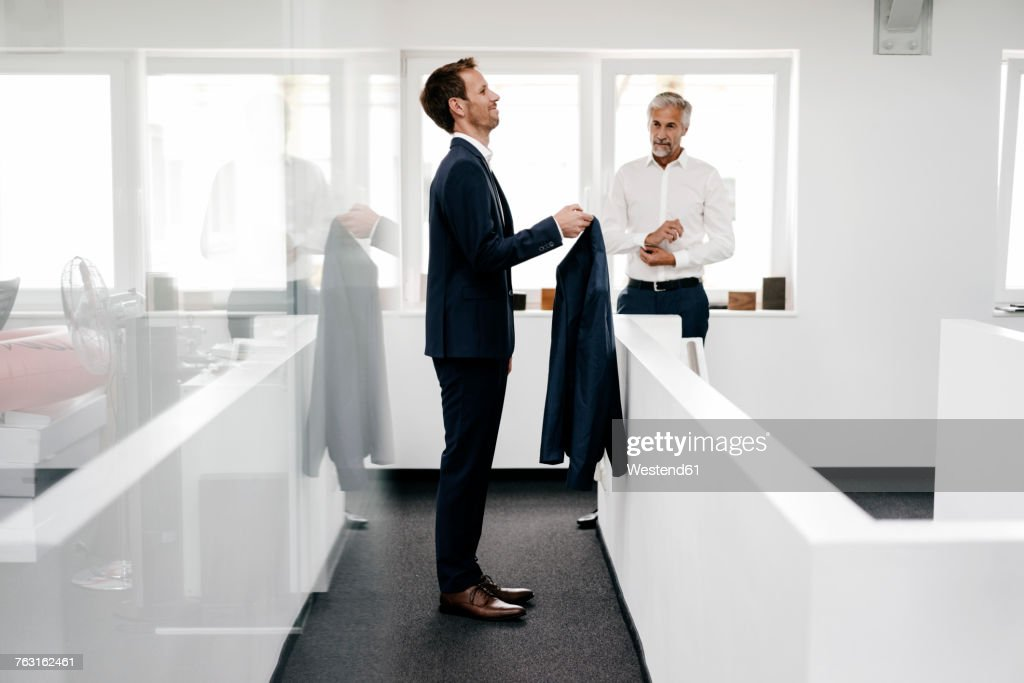 Employee in office holding jacket for his boss : Stock Photo