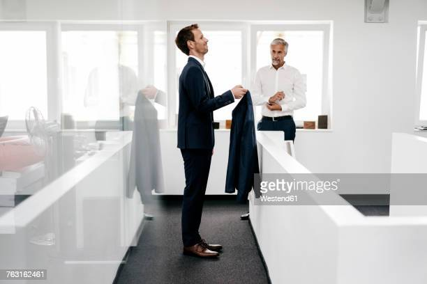 Employee in office holding jacket for his boss