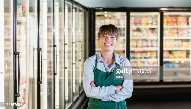 employee in refrigerated section of supermarket - employee stock pictures, royalty-free photos & images