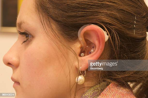 Employee Irina Baumeister poses wearing a Siemens hearingaid in a store in Bonn Germany on Wednesday Feb 10 2010 Siemens AG said it will review bids...