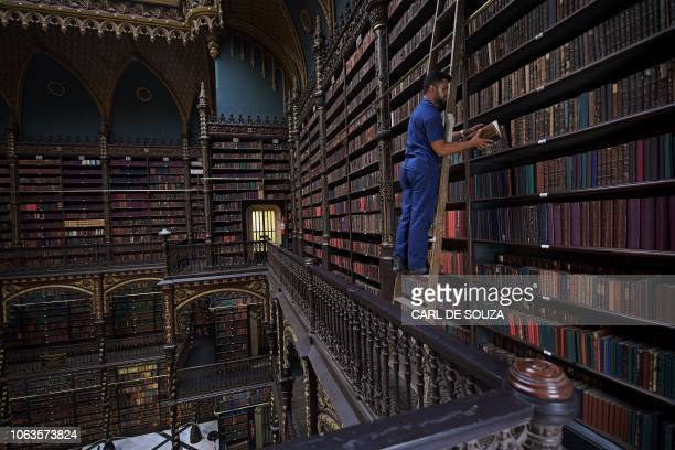TOPSHOT Employee Jeferson Deodata da Silva selects a book from the shelves of the Royal Portuguese Cabinet of Reading in Rio de Janeiro Brazil on...