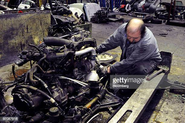 Employee Joao Carera works on a car engine at Allo Casse Auto's car demolition site in Athis Mons France on Wednesday Feb 24 2010 French consumer...