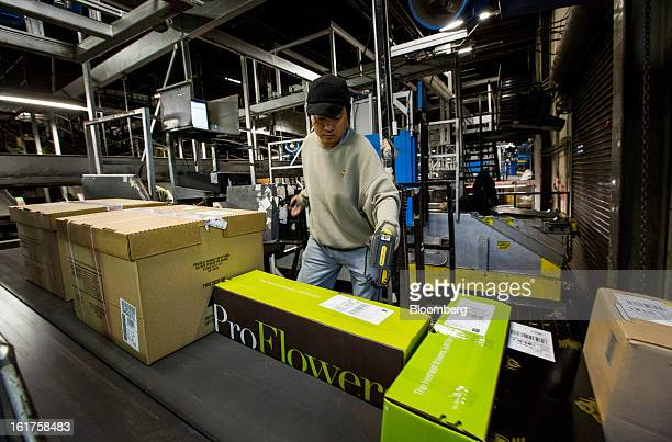 Employee Joseph Do scans packages unloaded from an air trailer at the United Parcel Service distribution center in Sacramento California US on...