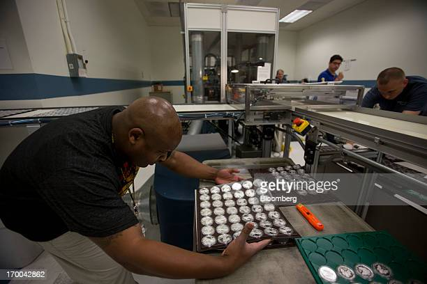 Employee Jumel Alston left works on the production line for one ounce silver bullion coins at the United States Mint at West Point in West Point New...