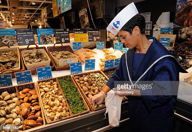 Employee Laldja Laidoudi selects shellfish at a Carrefour supermarket in Paris France on Thursday Aug 20 2009 Carrefour announce earnings next week