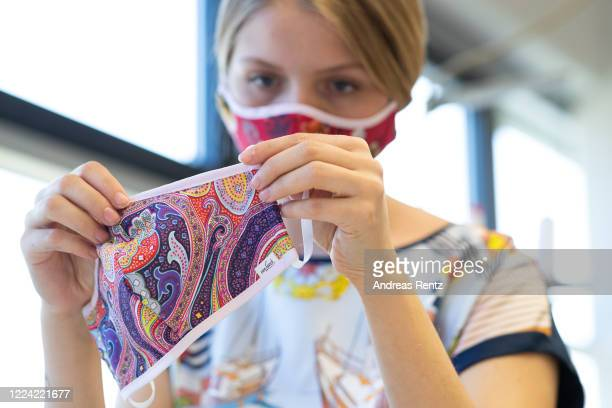 Employee Lea reviews a mask after she sew a protective face mask at the Van Laack fashion manufactory during the novel coronavirus crisis on May 08,...